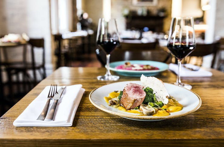 Two dishes and glasses of red wine on the table at Julios in West Perth