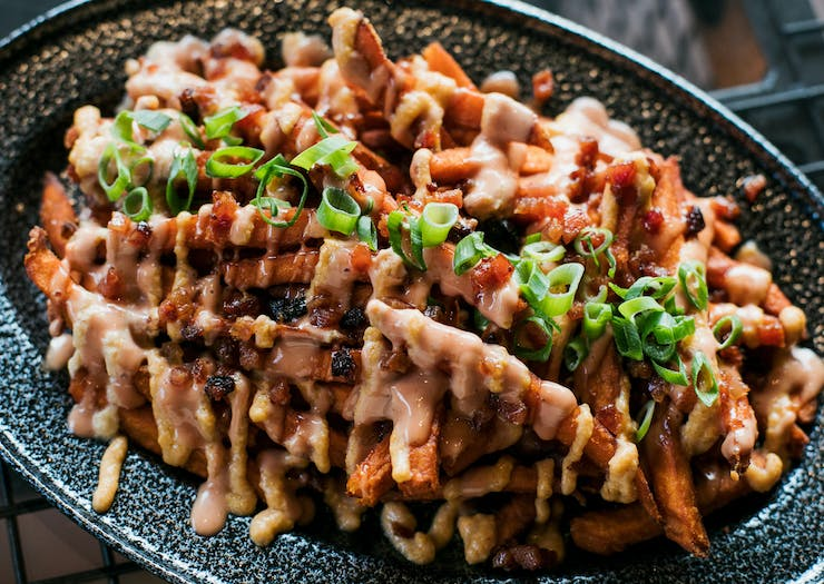Loaded fries covered in sauce.