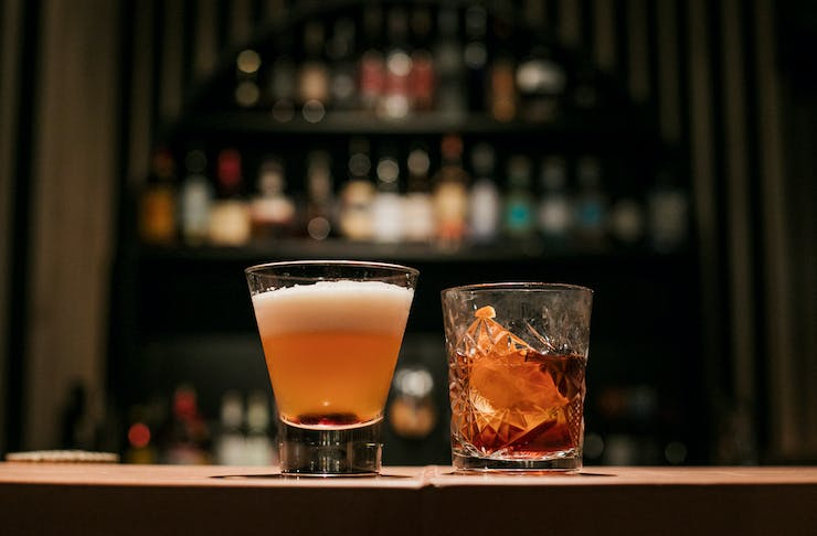 Two cocktails sit on a bar in a dim light.