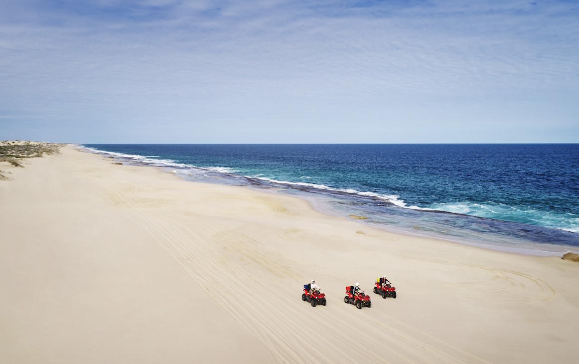Three people quad bike along the deserted beach in Kalbarri