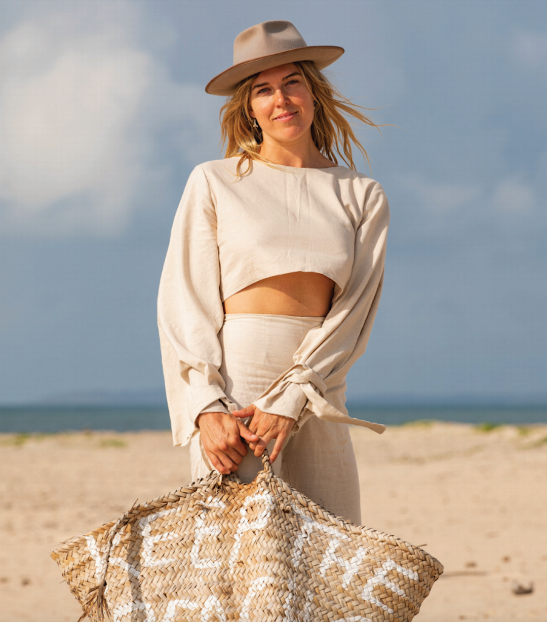 A woman stands smiling on the beach wearing a wide-brimmed hat holding a wicker bag.