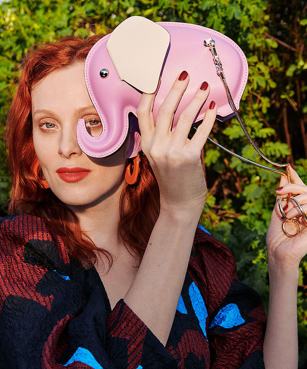 A woman with red hair holds up an elephant handbag by brand Kate Spade.