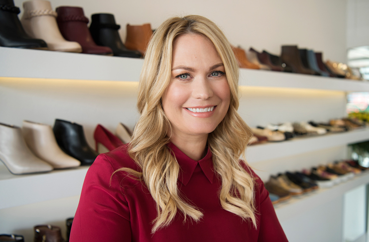 Kathryn Wilson sits in front of shelves of shoes she designed