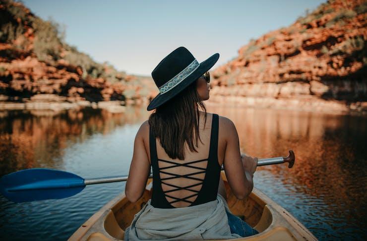 A woman kayaks along a calm lake in WA.