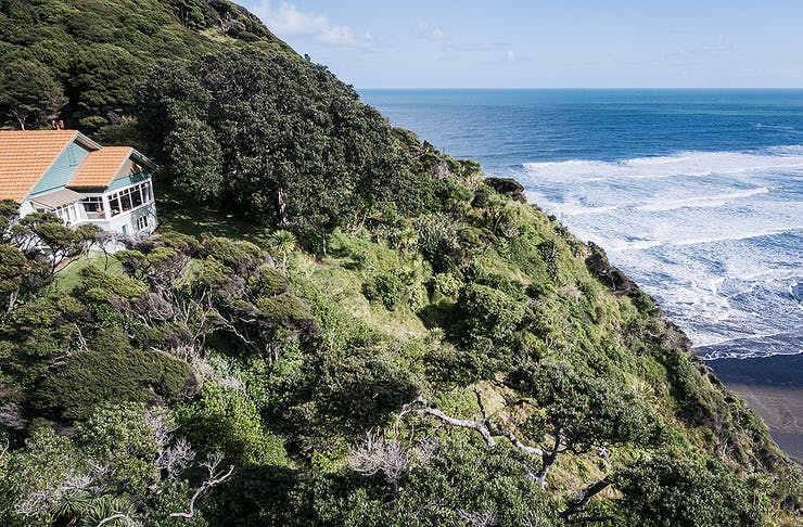 An orange-roofed 1930s heritage house sits on the side of a steep tree-covered hill, overlooking a bright blue seascape.