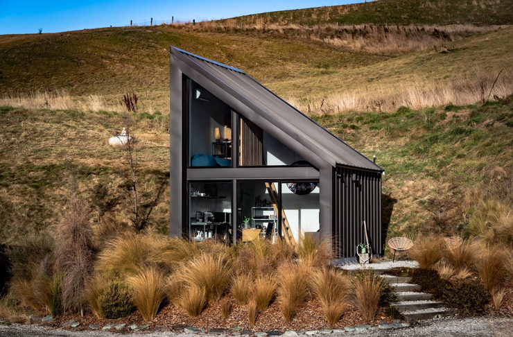 Grassy shrubs sit in front of this tiny home that has a roof shaped in a right angle triangle. Dry, grassy hills sit in the background