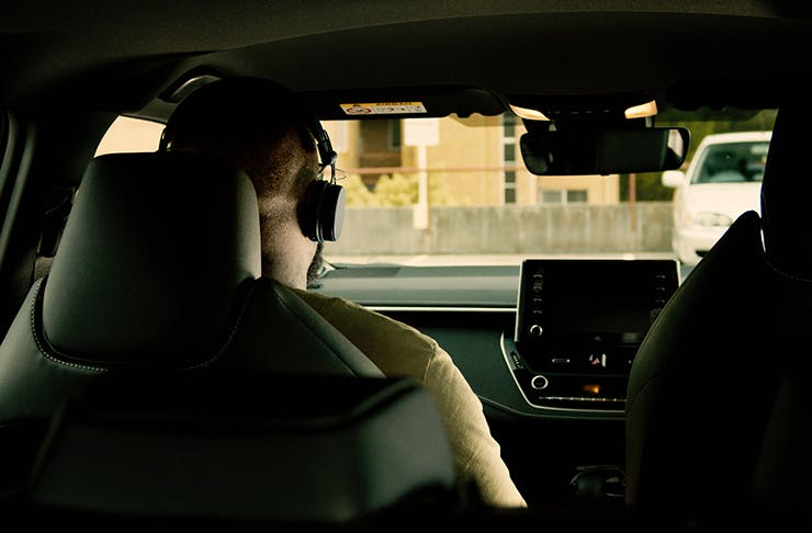 A shot from the backseat of a car with someone in the front seat wearing headphones.