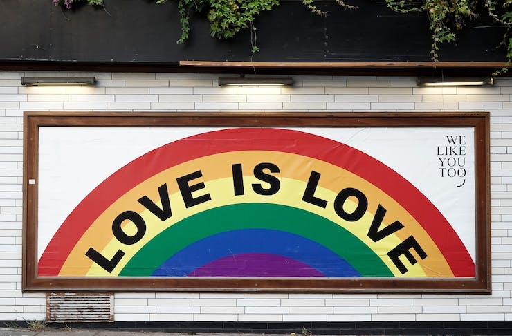 A white tiled wall with a painting of a rainbow with the words love is love written on the rainbow