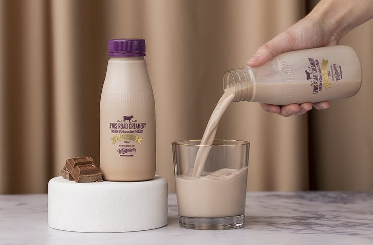 A person pours a glass of Lewis Road Lactose Free Chocolate milk.