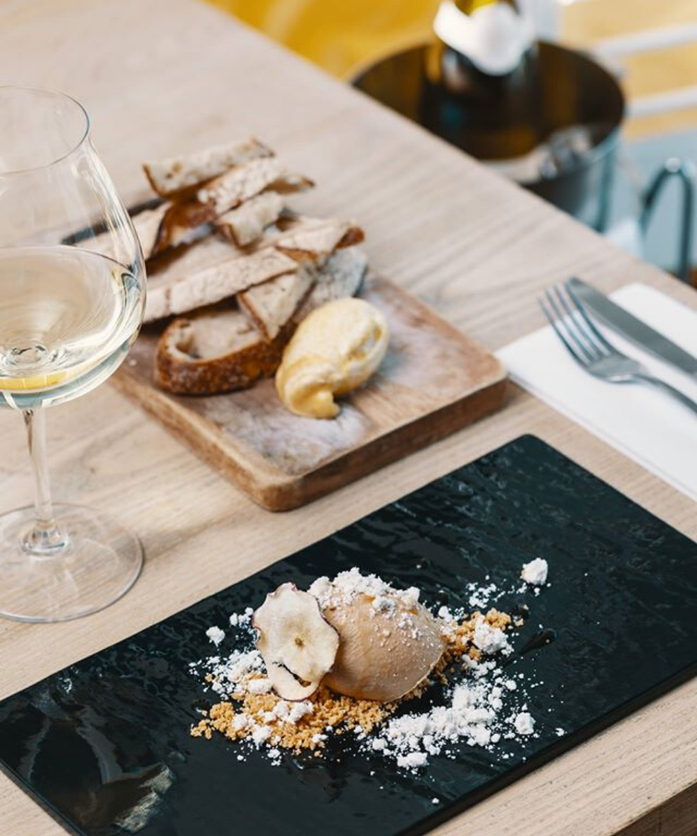 Wooden table with white wine, serving platter of sliced sourdough and beautiful presentation of gelato sitting on black plate with assortment of crushed biscuit