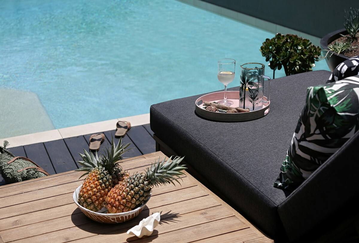 a day bed in front of a pool