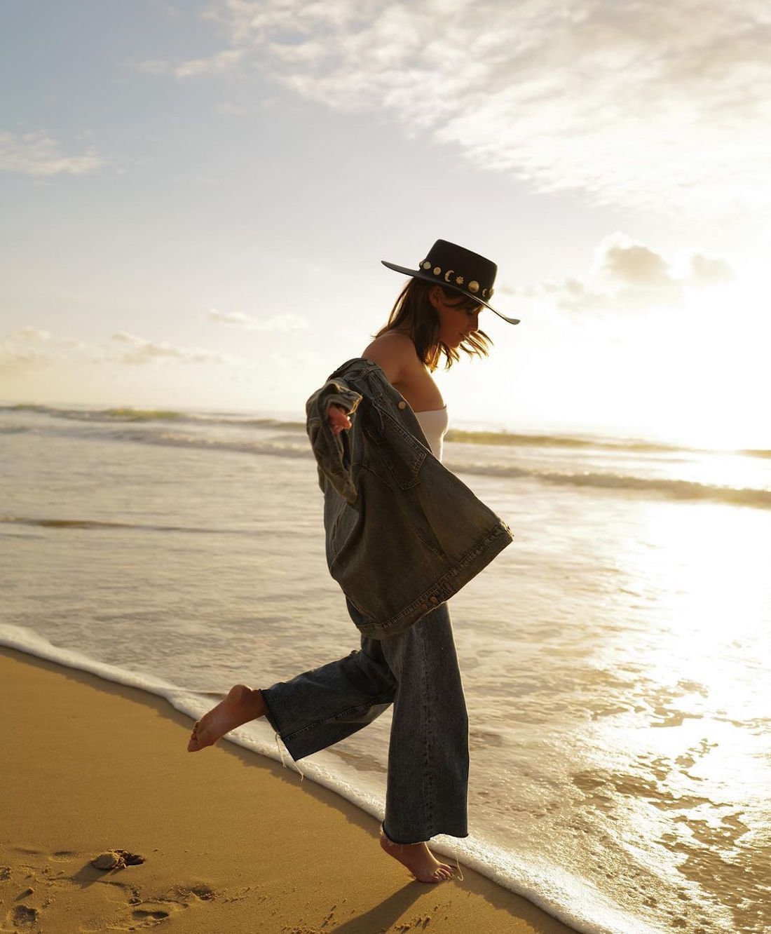 A woman walks on the beach wearing her Lack Of Colours hat.
