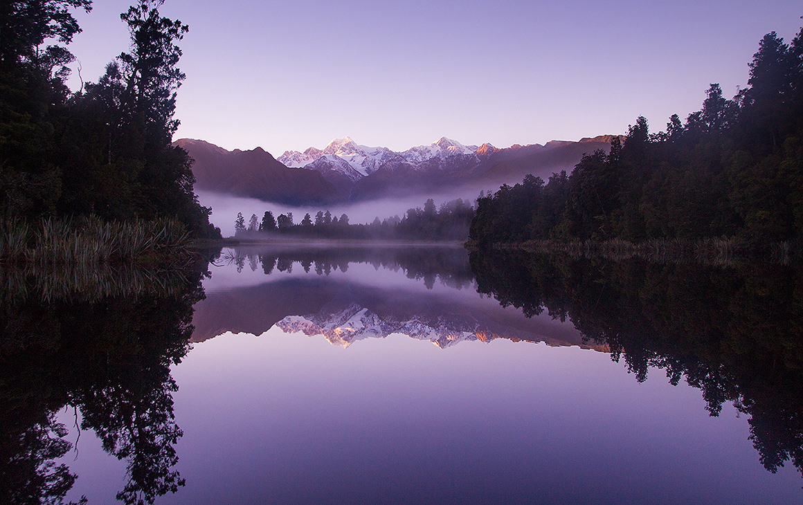 Lake Matheson with a purple hue seen at dusk.
