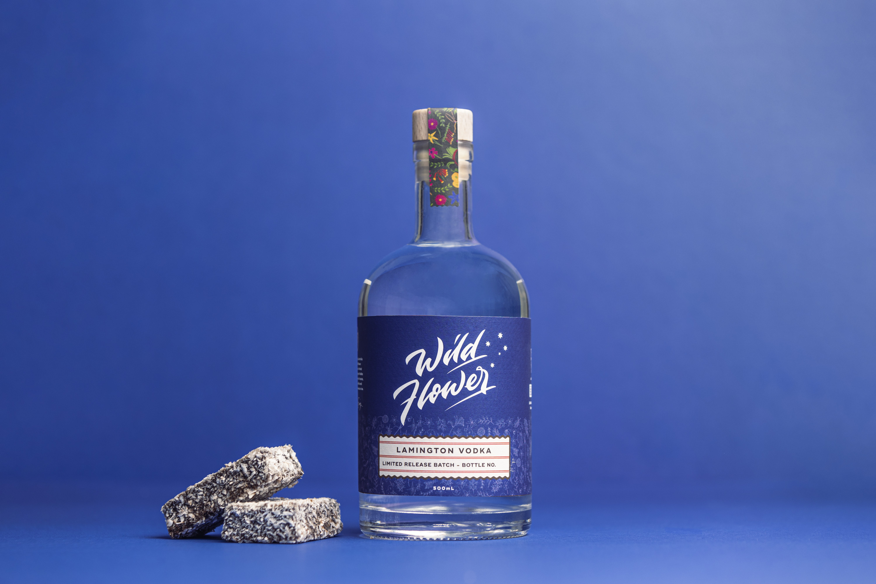 a bottle of lamington-flavoured wildflower gin next to two lamingtons against a blue background