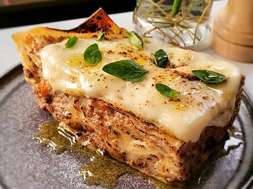 A piece of cheesy lasagna on a plate with basil on top.