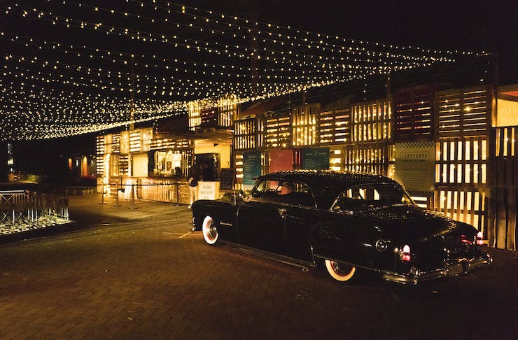 An old time car pulling up to a restaurant
