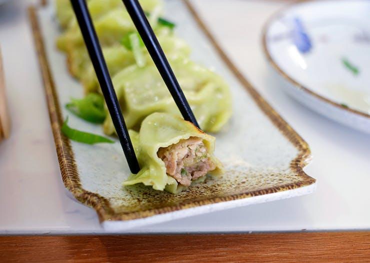 Chopsticks hold half eaten green dumpling