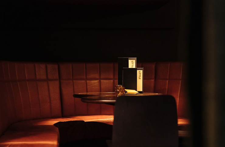 A table, menus and candles sit in the foreground with leather seating behind with intimate lighting