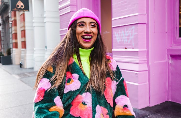 A woman wearing a colourful jacket stands in the street with a broad grin.