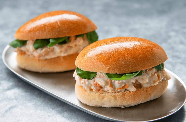 Two lobster rolls on a silver plate.