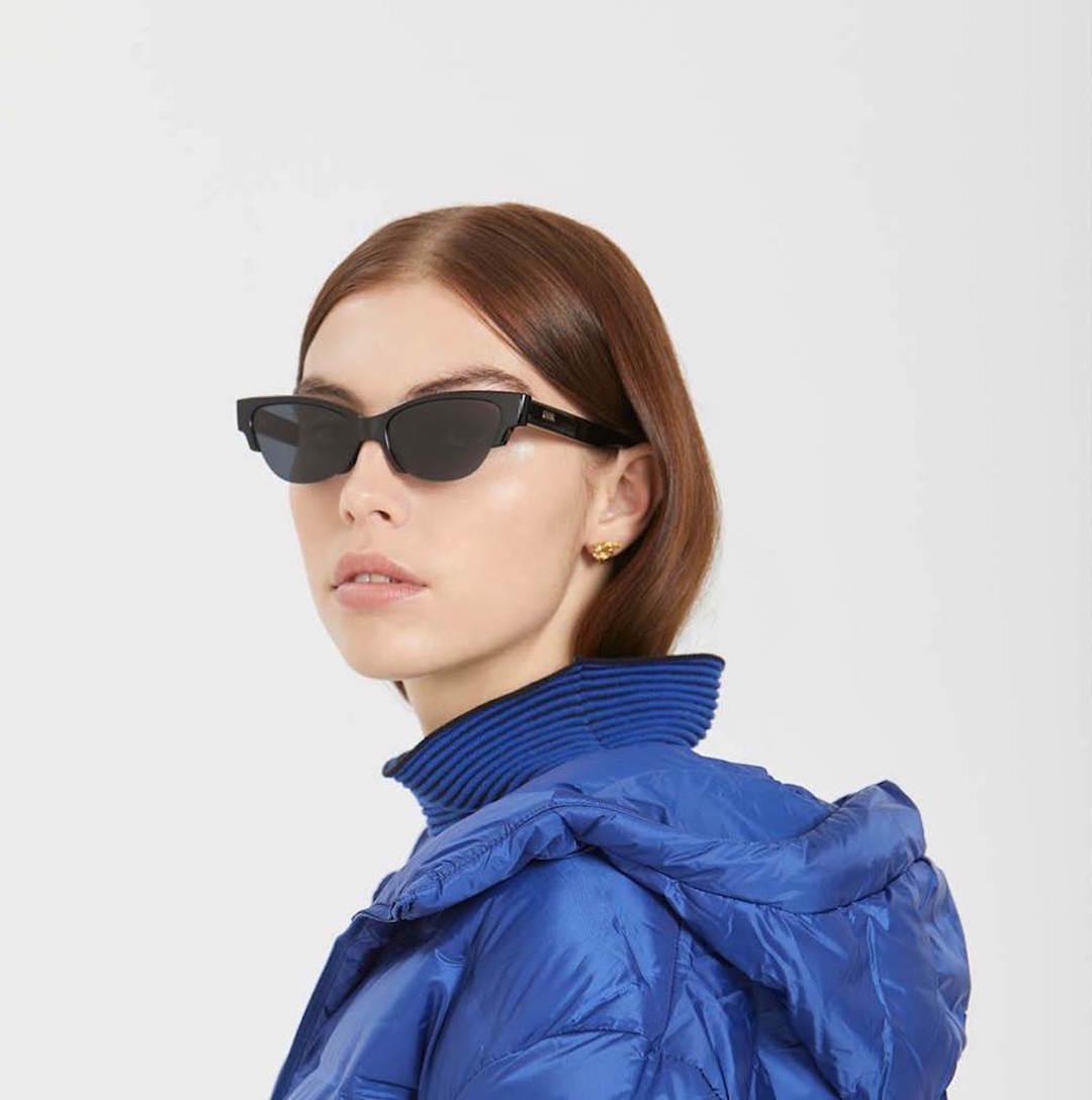 A woman wears a blue puffer jacket and sleek cateye sunglasses.