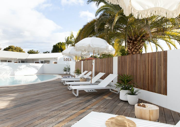 The pool area at LOEA Hotel, featuring sunbeams, white sun umbrellas and a timber deck.