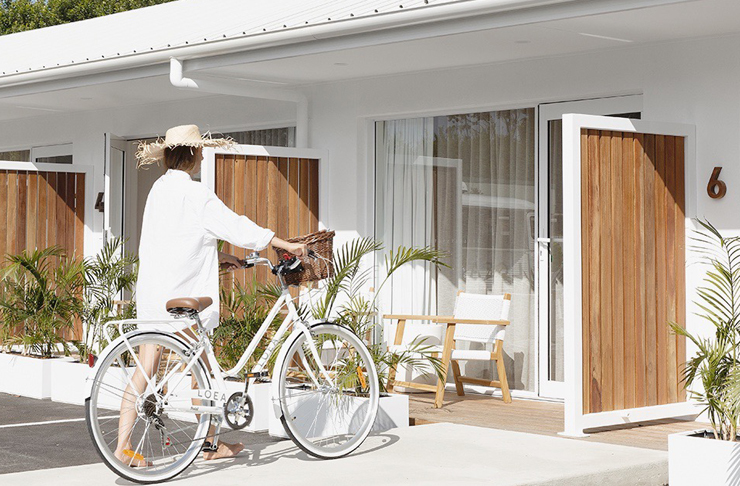Woman walking towards her room at LOEA Hotel on the Sunshine Coast, with a white cruiser bike.