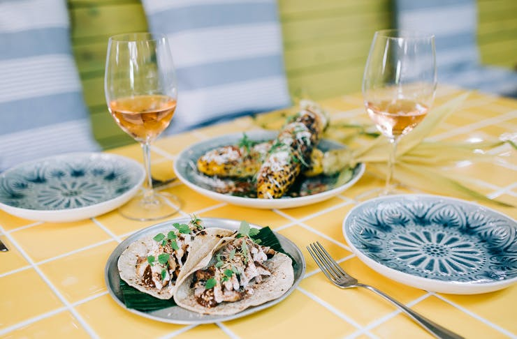 A yellow tiled table is filled with Mexican dishes and wine.