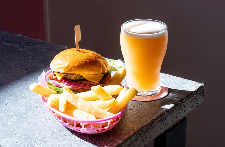a burger and fries in a basket and a pint of golden beer