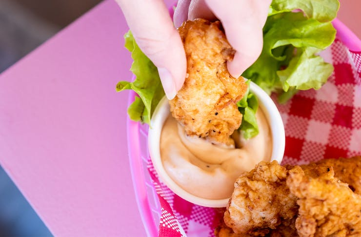 a fried chicken tender being dipped into a container of sauce on a pink table