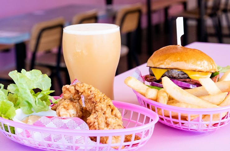 a burger, fried chicken pieces and a pint of beer on a pink table