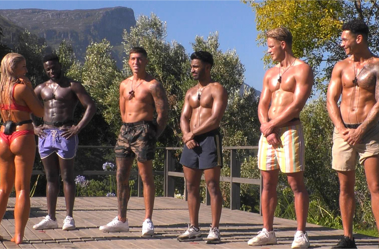Five super muscular men stand on trial whilst a woman passes judgement