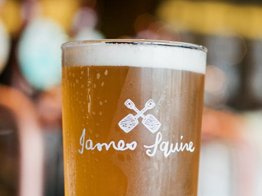 A pint glass of beer with the James Squire logo.