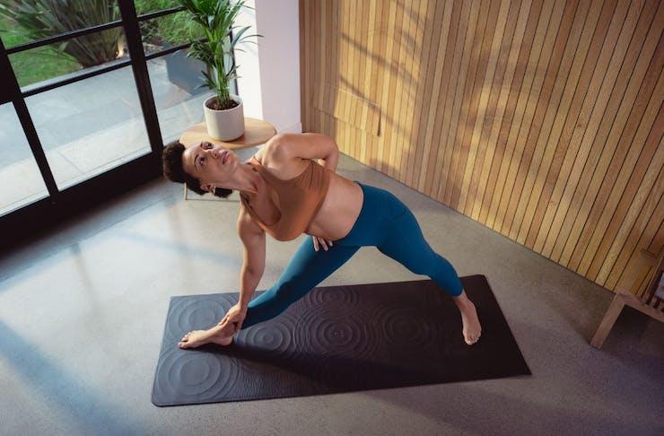 Woman doing yoga on a black mat
