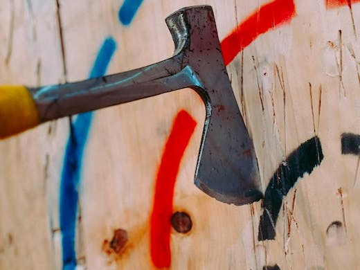 An axe wedged into a wooden wall target, from MANIAX, Sydney's axe throwing studio.