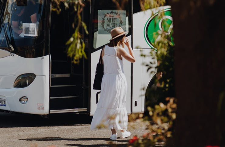 A woman in a white dress and a straw hat in front of the Merry Muster bus.