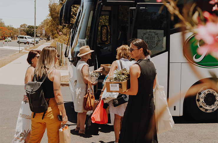 A group of women waiting to board a bus.