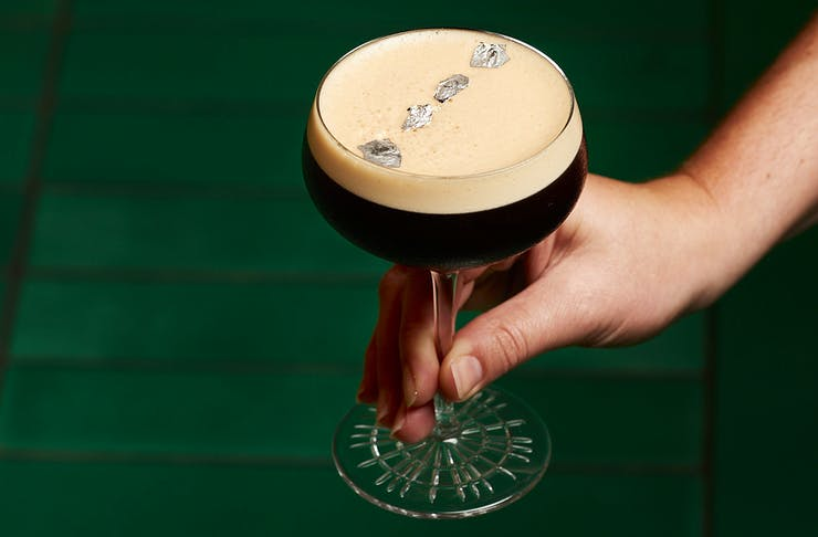 An espresso martini garnished with silver leaf stands on a green table.