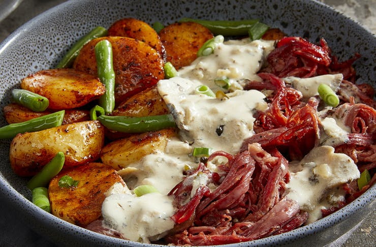 A steamy bowl of potato, greens and beef brisket.
