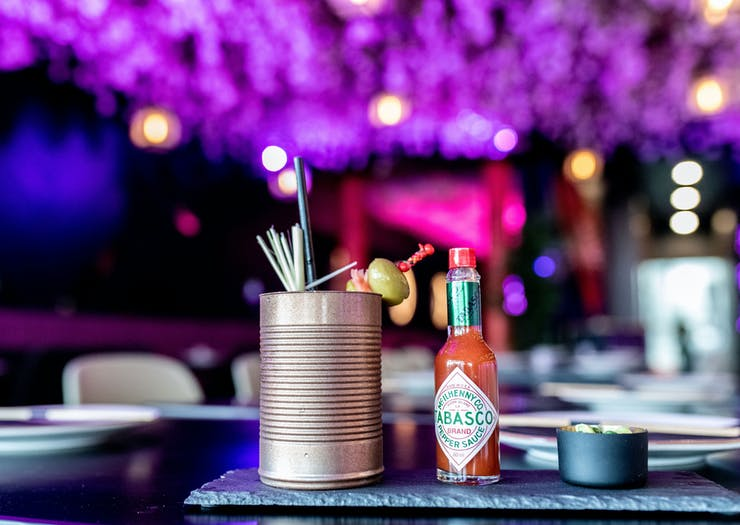 A Bloody Mary style cocktail served in a tin can with a bottle of Tabasco beside it, against a neon-purple backdrop.