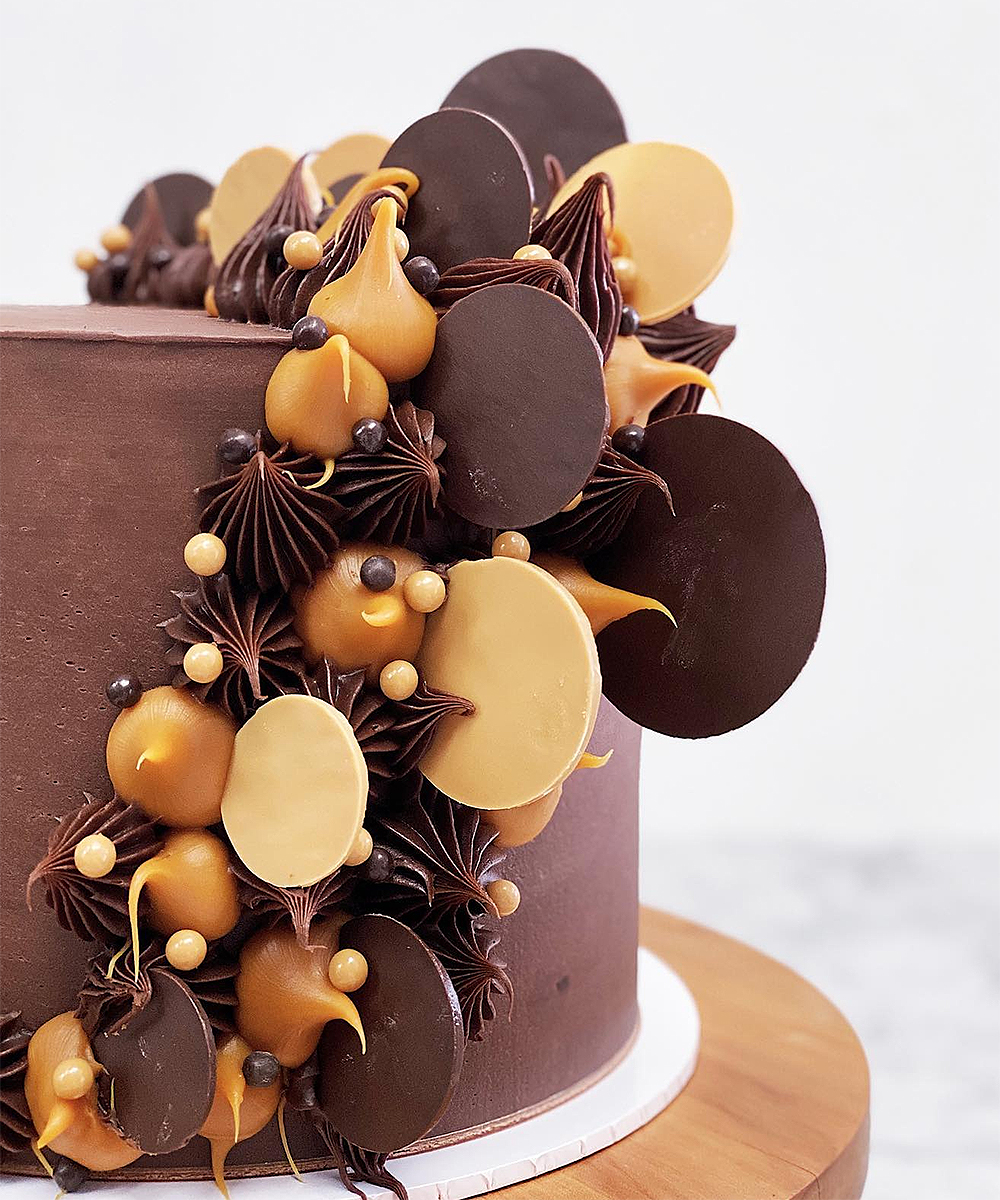 Rich chocolate layered with salted caramel ganache and dark chocolate ganache and decorated with dark chocolate and dulce chocolate disks, dollops and chocolate pearls from Magnolia Kitchen.
