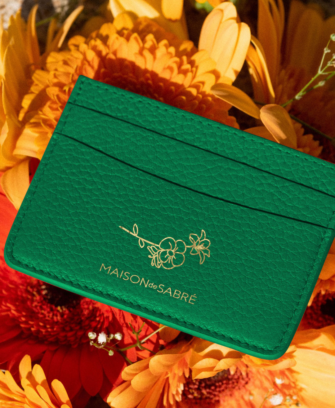 An emerald green cardholder lays on a bed of flowers.