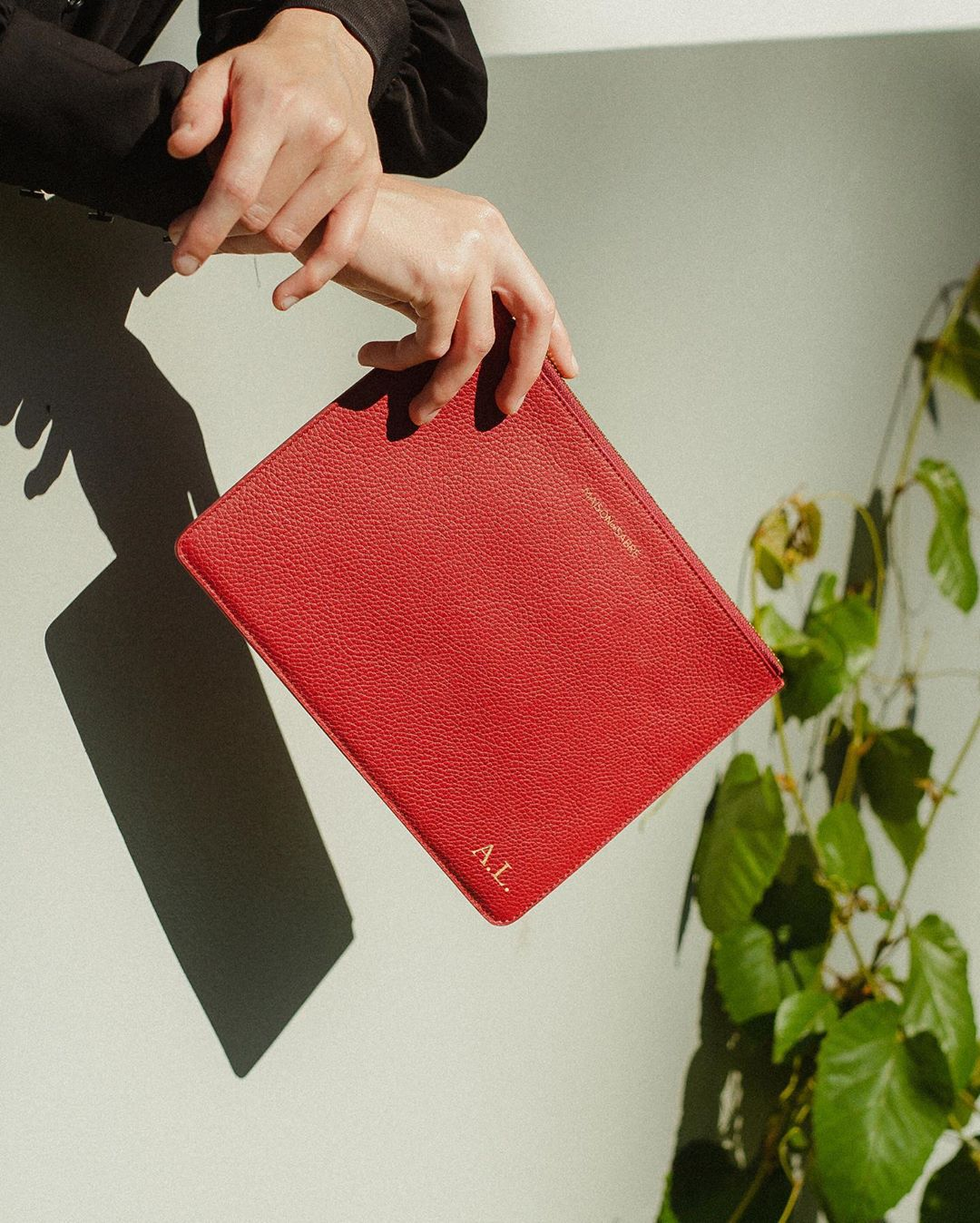 A woman holds are arms crossed with a red leather clutch.