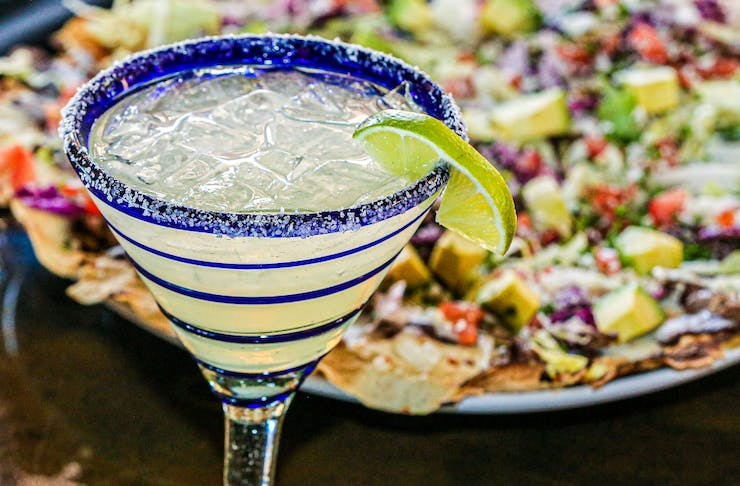 A margarita in a glass with blue stripes sits in front of a plate of nachos