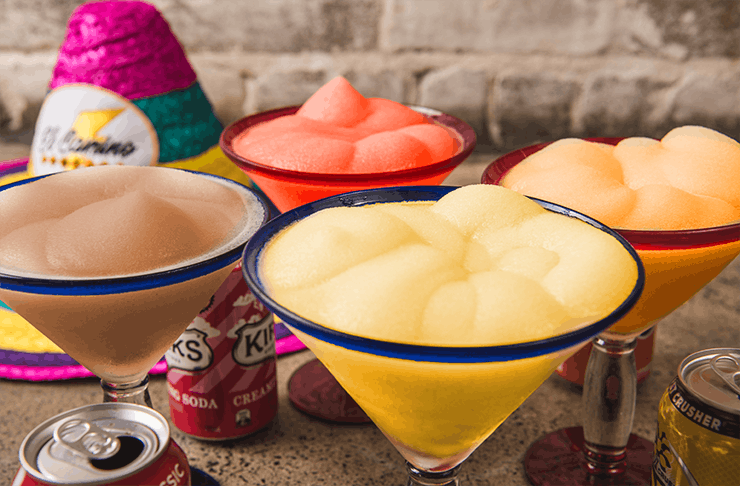 Four different coloured Margaritas with different soft drink cans around.