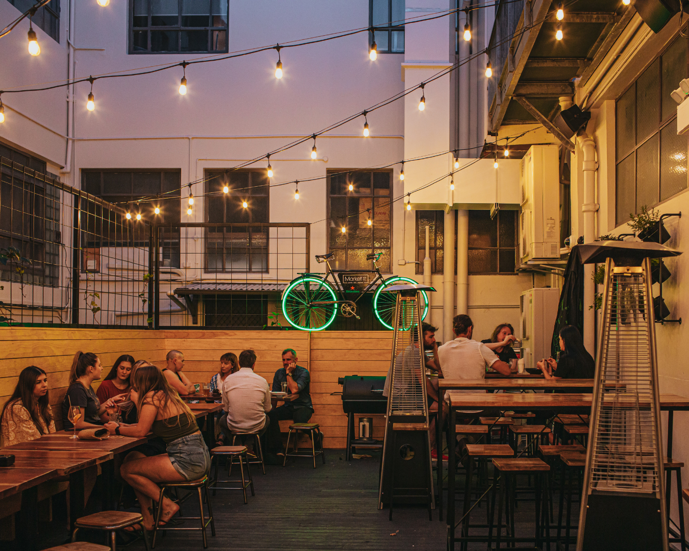 Customers enjoying drinks at the outdoor area of the bar. A cycle with green neon lights hangs on the fence.