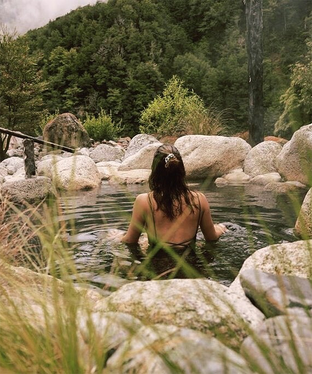 A girl sits in the water at Maruia Hot Springs