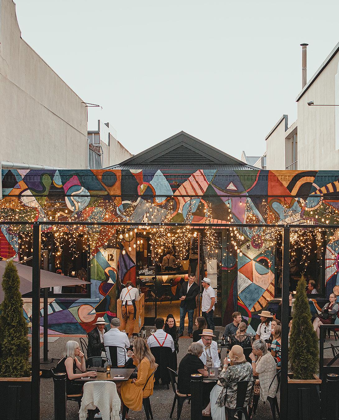 People enjoying alfresco dining at a well lit wine bar.
