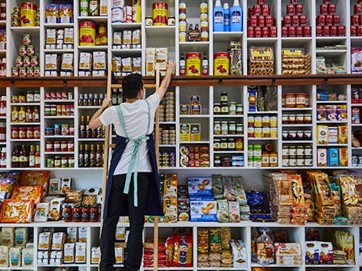 A man reaching on a step to a packet of pasta amongst a wall of different goods.