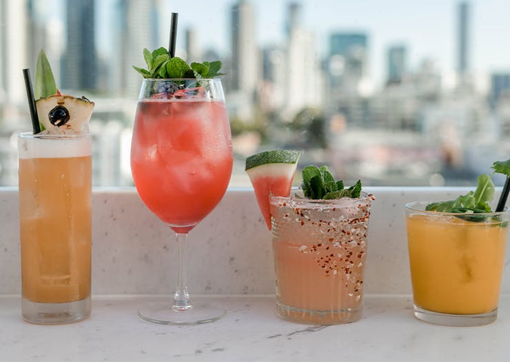 4 cocktails in a row on a bench overlooking the city.
